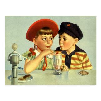 Niños, muchacho y chica del vintage compartiendo postal