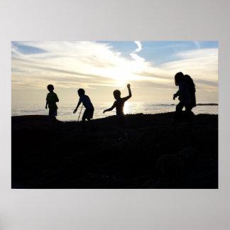 Niños que exploran en roca de la playa en la póster