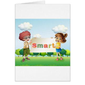 Niños sonrientes que sostienen un letrero tarjeta de felicitación