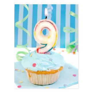 Novenas velas del cumpleaños en la torta helada en postal