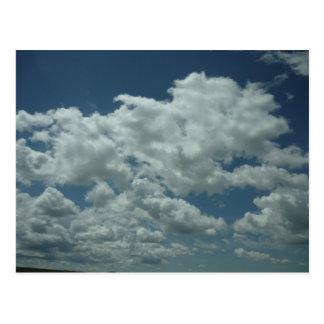 Nubes blancas, mullidas en cielo azul postal