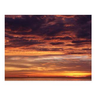 Nubes oscuras en cielo rayado naranja postal