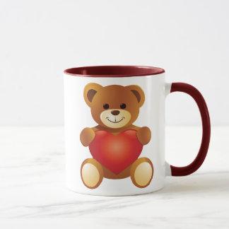 Oso lindo precioso que lleva a cabo un corazón del taza