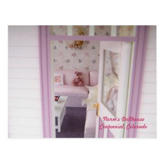Oso miniatura en una cabaña miniatura postal