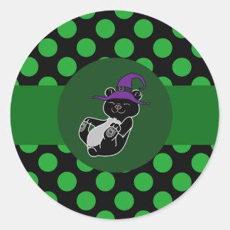 Oso negro con el gorra de la bruja y los puntos pegatina redonda