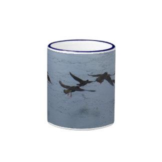 Ostreros en vuelo sobre el agua taza de café