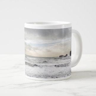 Paisaje marino espumoso pálido del océano, taza de café grande
