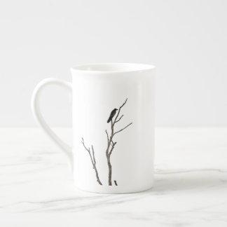 Pájaro en una taza de la porcelana de hueso de la