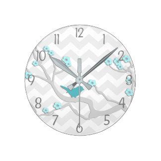 Pájaro gris de la aguamarina del trullo en el reloj redondo mediano