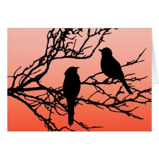 Pájaros en una rama, negra contra el naranja de la tarjeta pequeña
