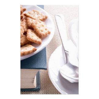Papelería Placa blanca con las galletas en el libro viejo