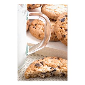 Papelería Taza de cristal con las galletas de la leche y de