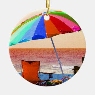 Parasol de playa y sillas invertidos coloridos en adorno redondo de cerámica