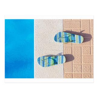 Pares de deslizadores en el borde de la piscina postal