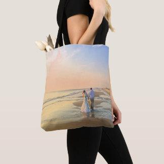 Pares del boda en la bolsa de asas de la playa