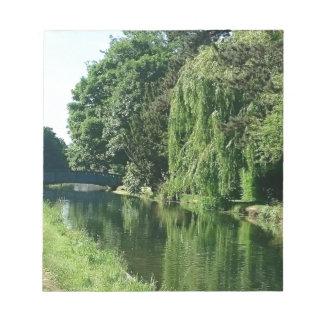 Paseo soleado verde del río de los árboles del bloc de notas