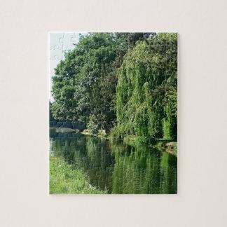 Paseo soleado verde del río de los árboles del puzzle