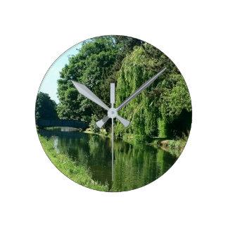 Paseo soleado verde del río de los árboles del reloj redondo mediano