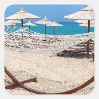 Pegatina Cuadrada Hamaca con los parasoles de playa en la costa