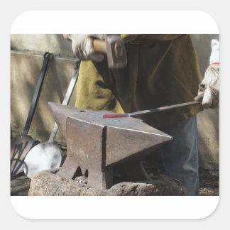 Pegatina Cuadrada Herrero que forja manualmente el metal fundido