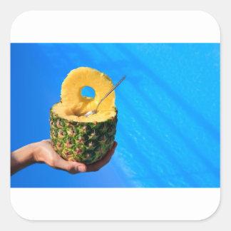 Pegatina Cuadrada Mano que sostiene la piña fresca sobre piscina