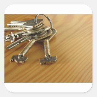Pegatina Cuadrada Manojo de llaves gastadas de la casa en la tabla