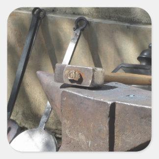 Pegatina Cuadrada Martillo del herrero que descansa sobre el yunque