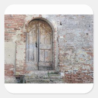 Pegatina Cuadrada Puerta de madera vieja en pared de ladrillo vieja