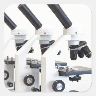 Pegatina Cuadrada Tres microscopios en una fila aislada en fondo