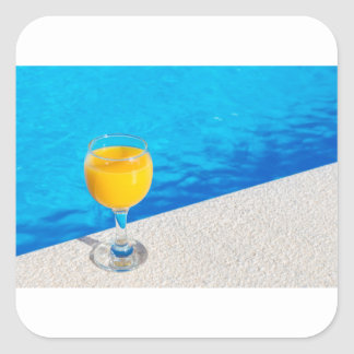 Pegatina Cuadrada Vidrio con el zumo de naranja en el borde de la
