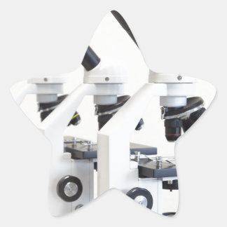 Pegatina En Forma De Estrella Tres microscopios en una fila aislada en fondo