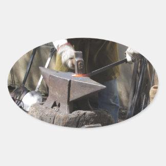 Pegatina Ovalada Herrero que forja manualmente el metal fundido