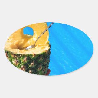 Pegatina Ovalada Mano que sostiene la piña fresca sobre piscina