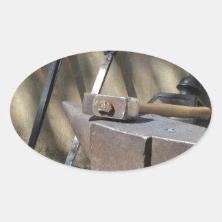 Pegatina Ovalada Martillo del herrero que descansa sobre el yunque