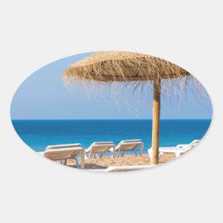 Pegatina Ovalada Parasol de mimbre con la playa beds.JPG