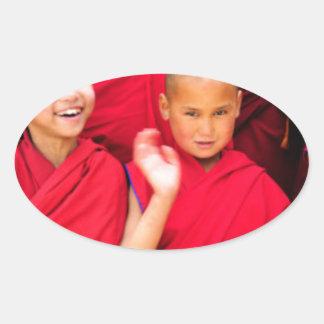 Pegatina Ovalada Pequeños monjes en trajes rojos