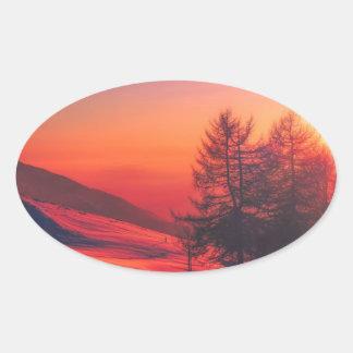 Pegatina Ovalada Puesta del sol de la tarde Nevado