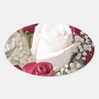Pegatina Ovalada ramo de rosas rojos con un rosa blanco en el
