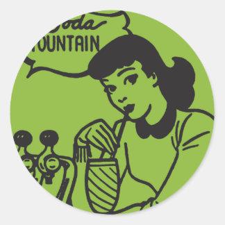 Pegatina Redonda Chica que bebe en la fuente de soda