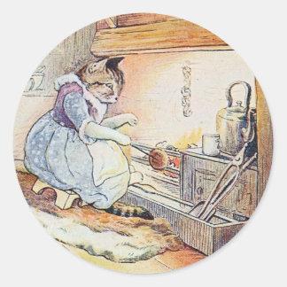 Pegatina Redonda El gato del gatito se sienta por el fuego