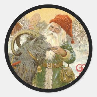 Pegatina Redonda Jultomten alimenta a cabra de Yule una galleta