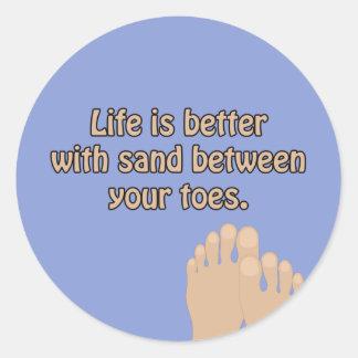 Pegatina Redonda La arena de la playa toca con la punta del pie al