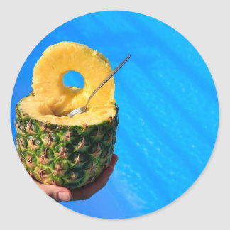 Pegatina Redonda Mano que sostiene la piña fresca sobre piscina