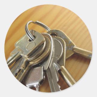 Pegatina Redonda Manojo de llaves gastadas de la casa en la tabla