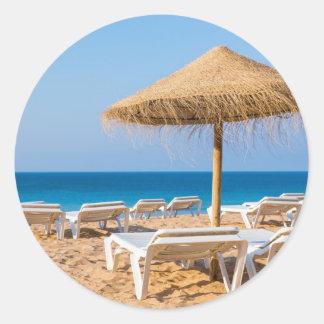 Pegatina Redonda Parasol de mimbre con la playa beds.JPG