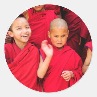 Pegatina Redonda Pequeños monjes en trajes rojos