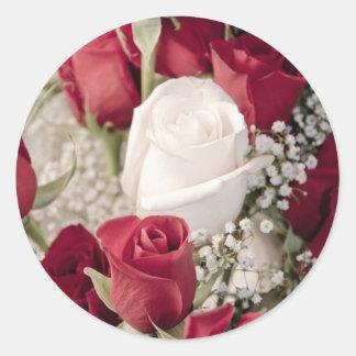 Pegatina Redonda ramo de rosas rojos con un rosa blanco en el