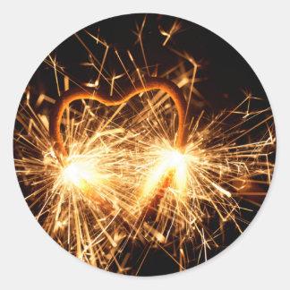 Pegatina Redonda Sparkler ardiente en forma de un corazón