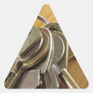 Pegatina Triangular Manojo de llaves gastadas de la casa en la tabla