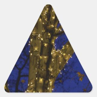 Pegatina Triangular Ramas con luces de navidad y un cielo azul marino